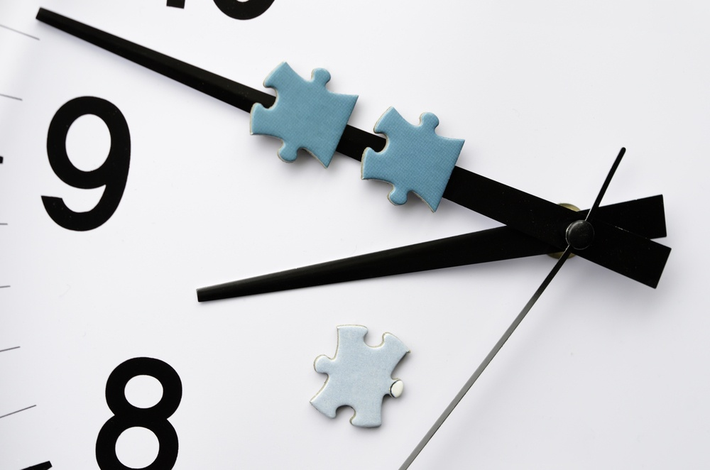 Delivery time Minute hand of analog electric clock carries two pieces of jigsaw puzzle, with a third on the white face.jpeg